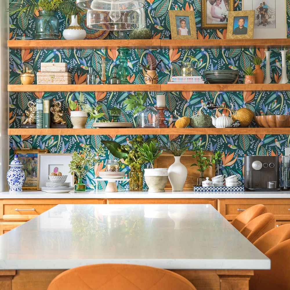 A kitchen lined with shelves and printed wallpaper