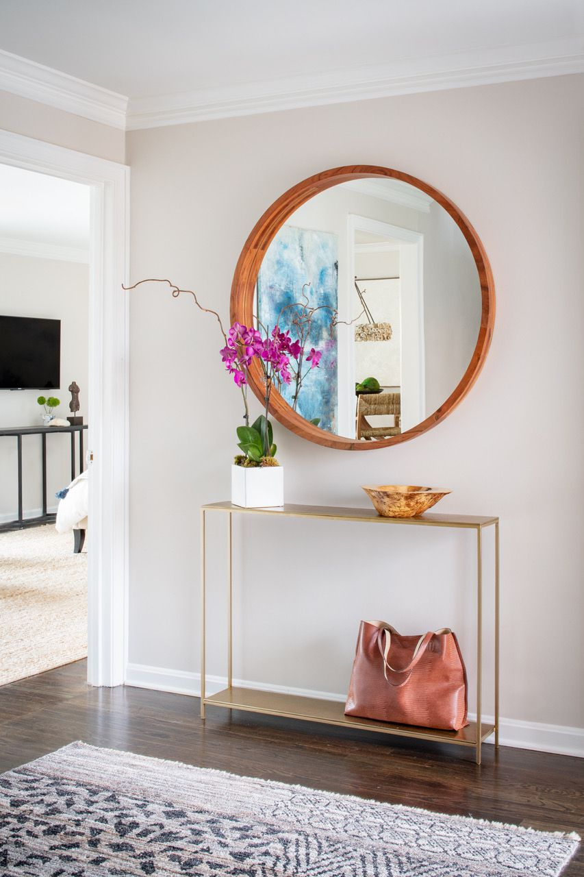 Liz Mearns home tour - entryway with gold console and round mirror