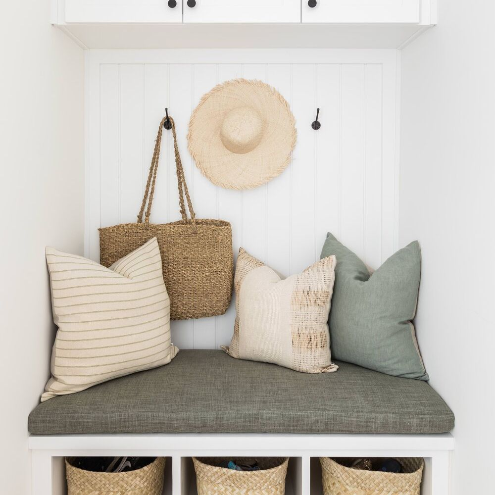 A small mudroom with a bench, several hooks, and a few baskets