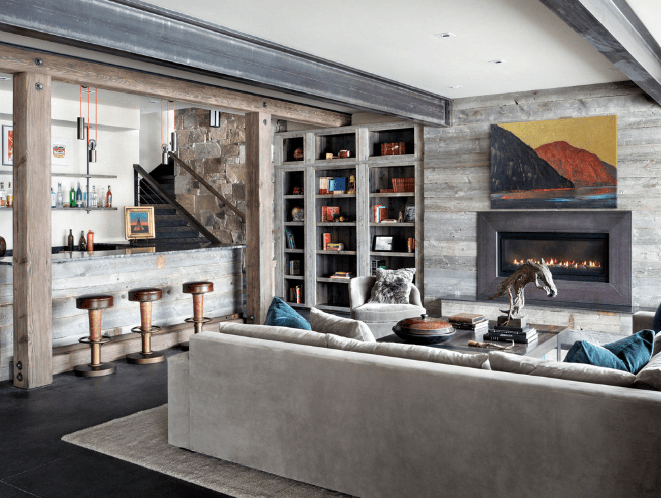 A basement with a built-in bar lit by two striking pendant lights