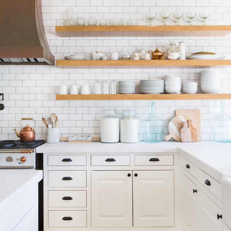 A white kitchen with organized shelves and counters