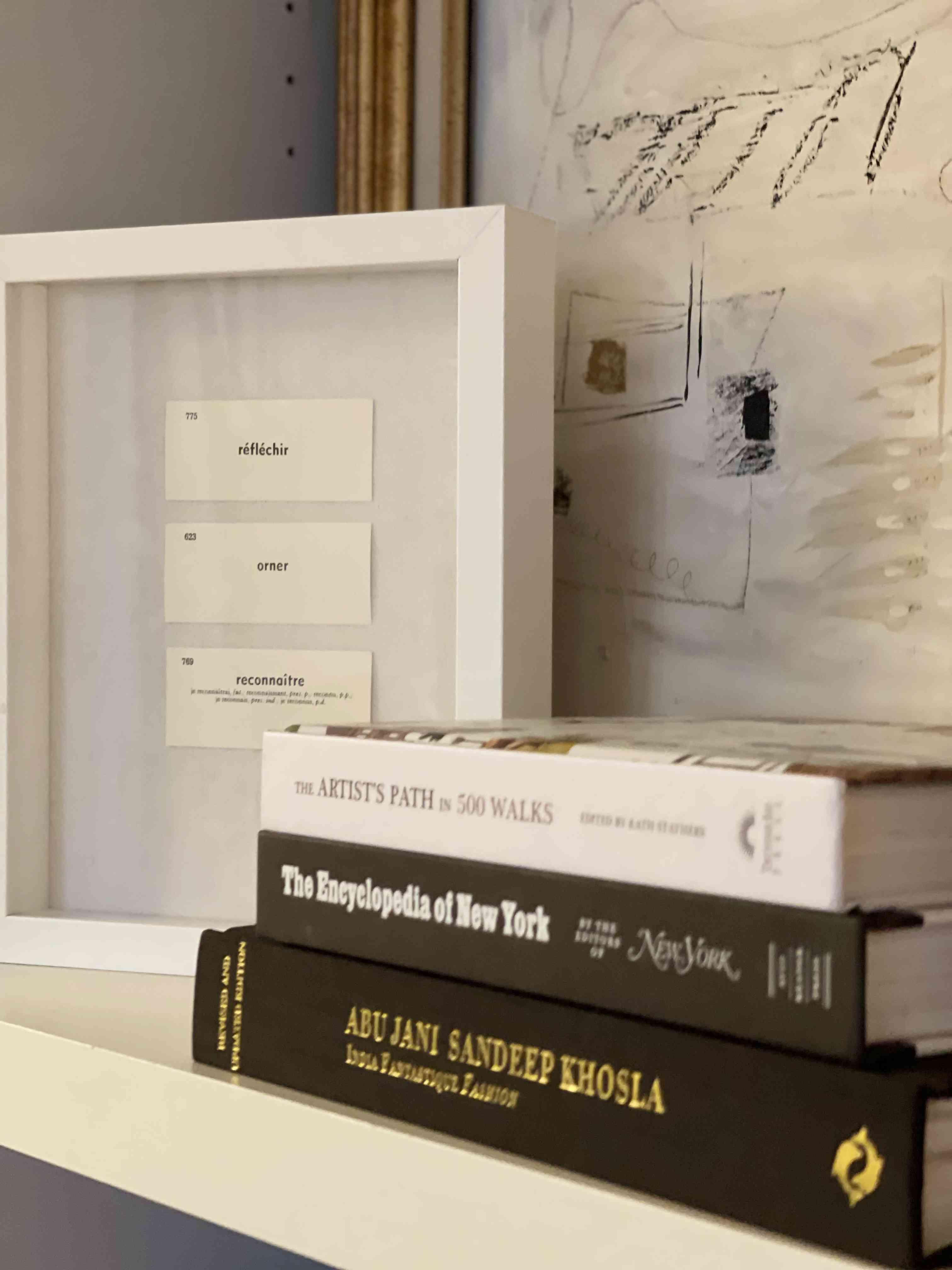 Shadowbox next to coffee table books.