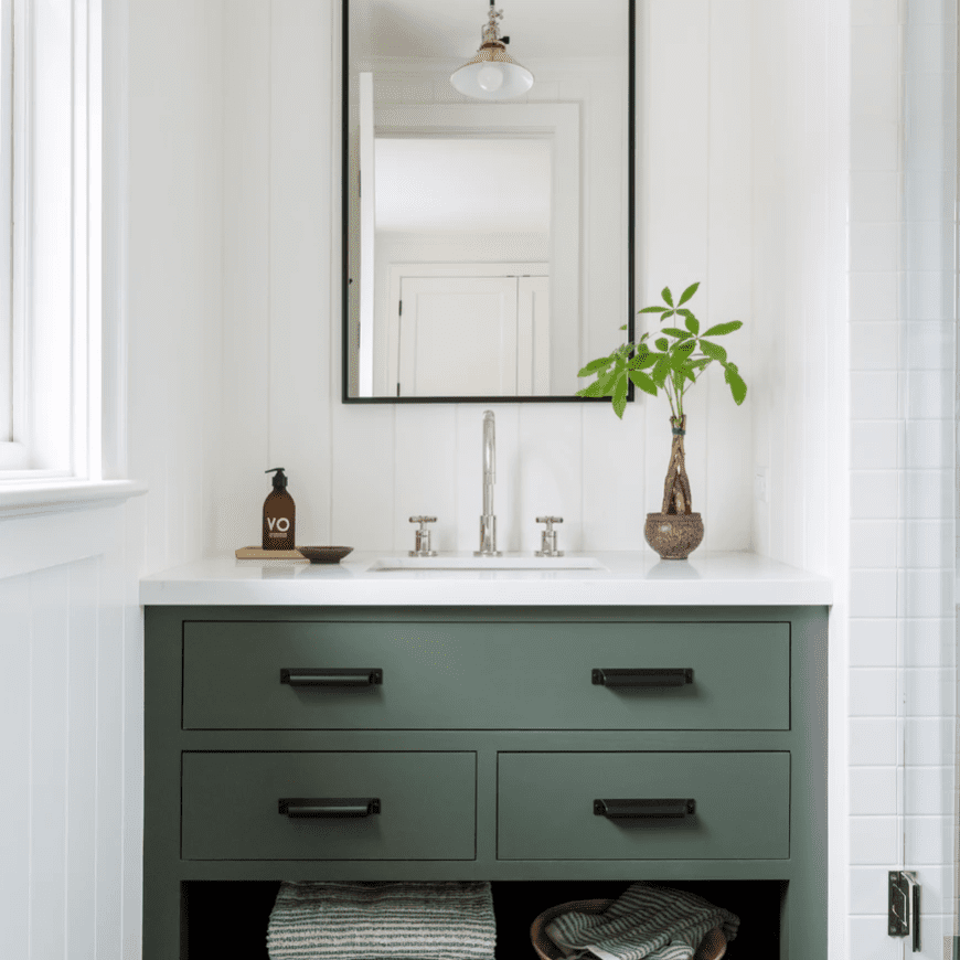A bathroom with green cabinets