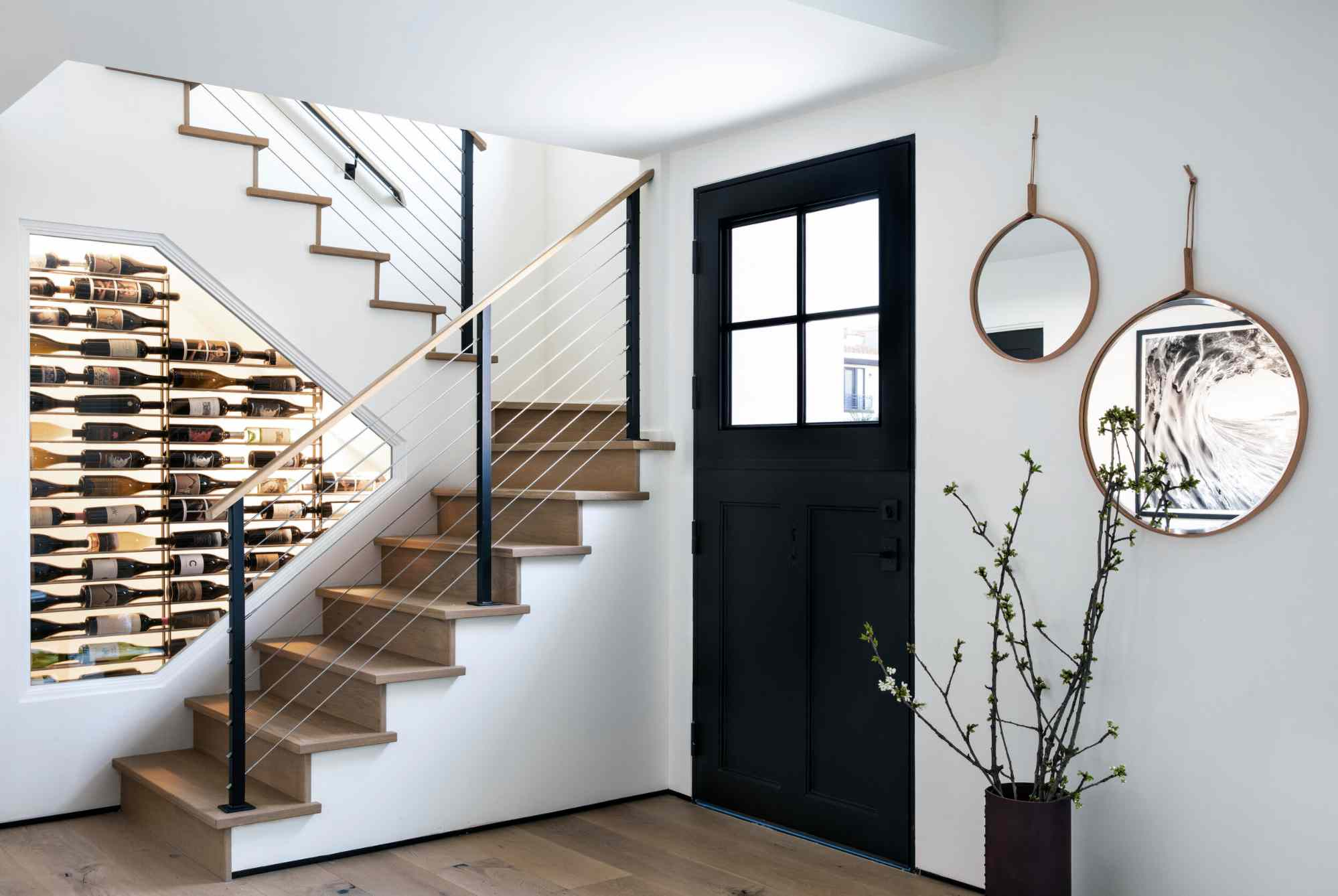 entryway with black door, white walls, stairs with a wine collection displayed inside the wall