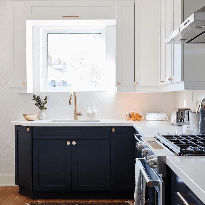 White and blue kitchen with white scalloped backsplash.