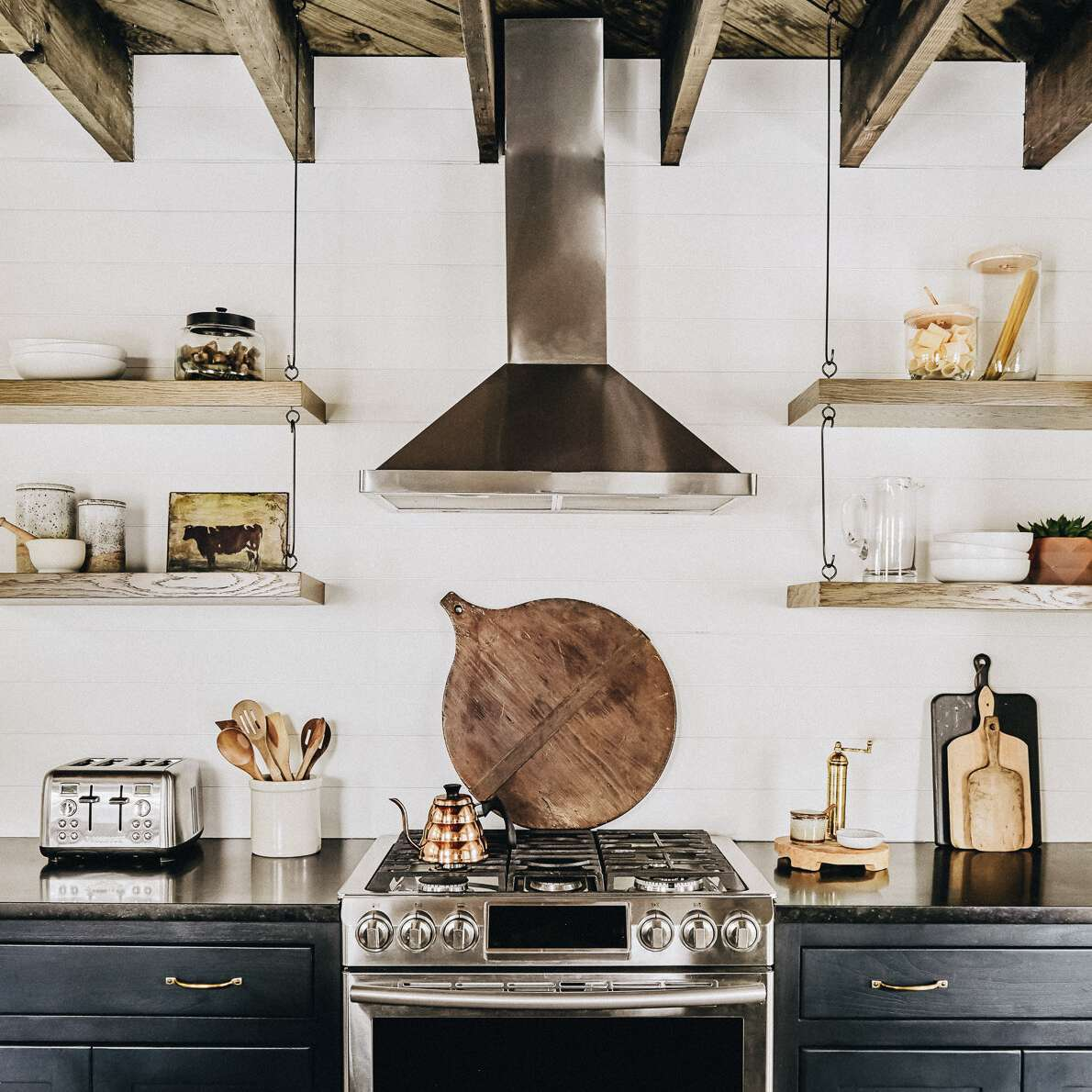 A rustic kitchen with shelves hanging from the ceiling