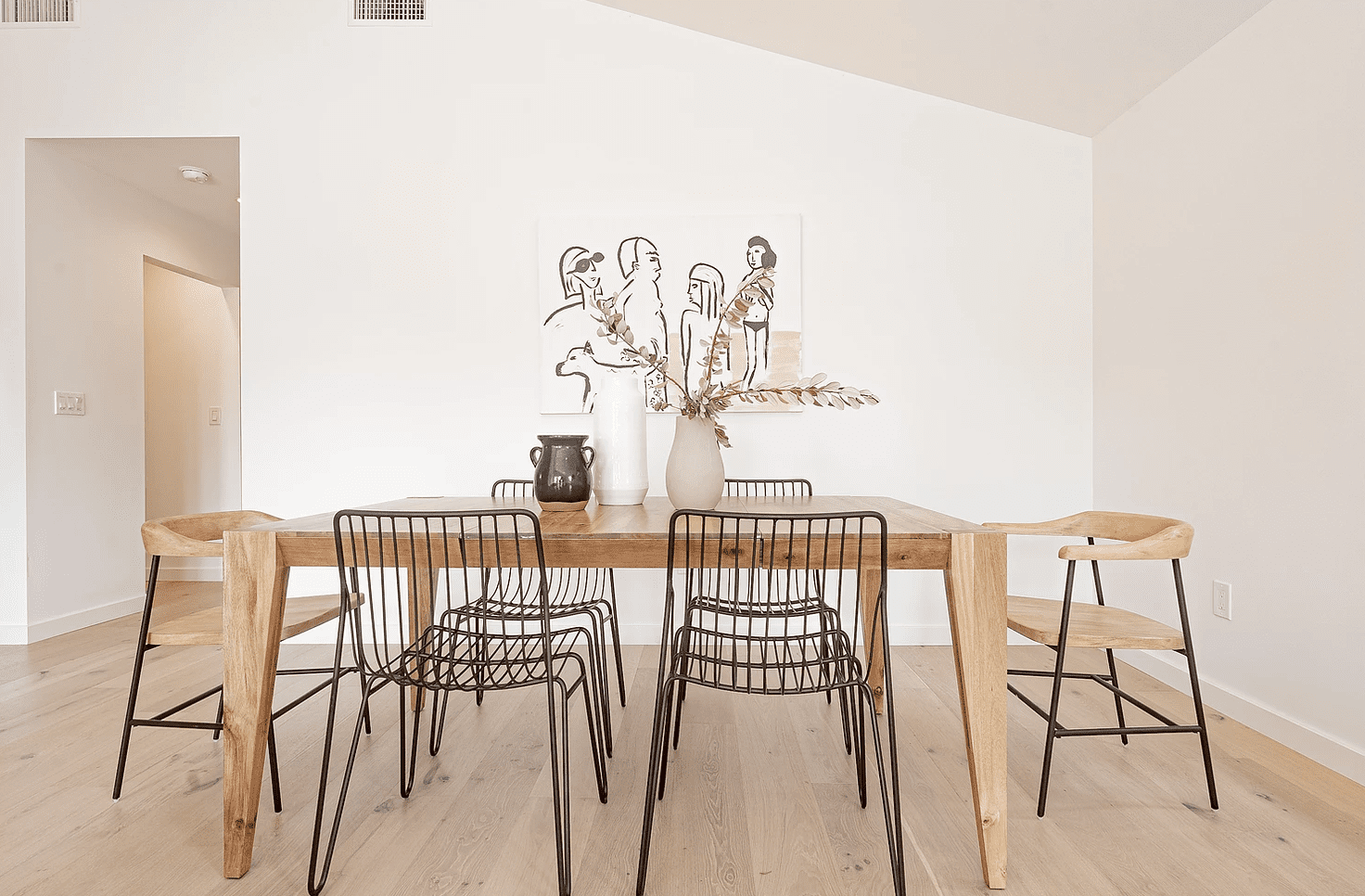 A wooden dining room table topped with three neutral vases