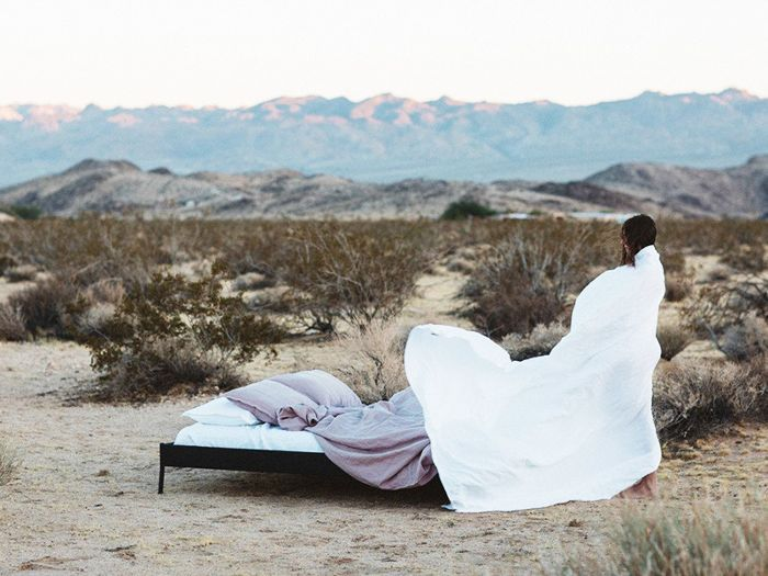 a bed with Morrow linen bedding out in the desert