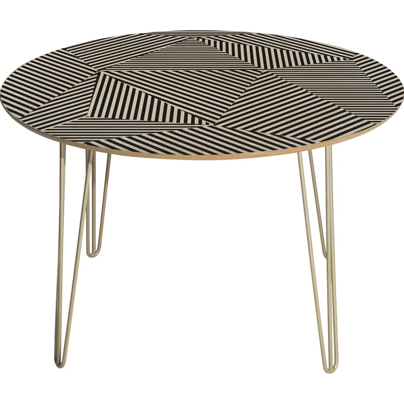 A round table with a graphic black and white print on top and gold tone hairpin legs.