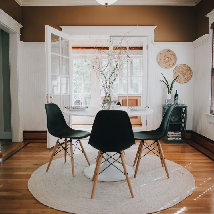 Neutral dining room with black chairs.