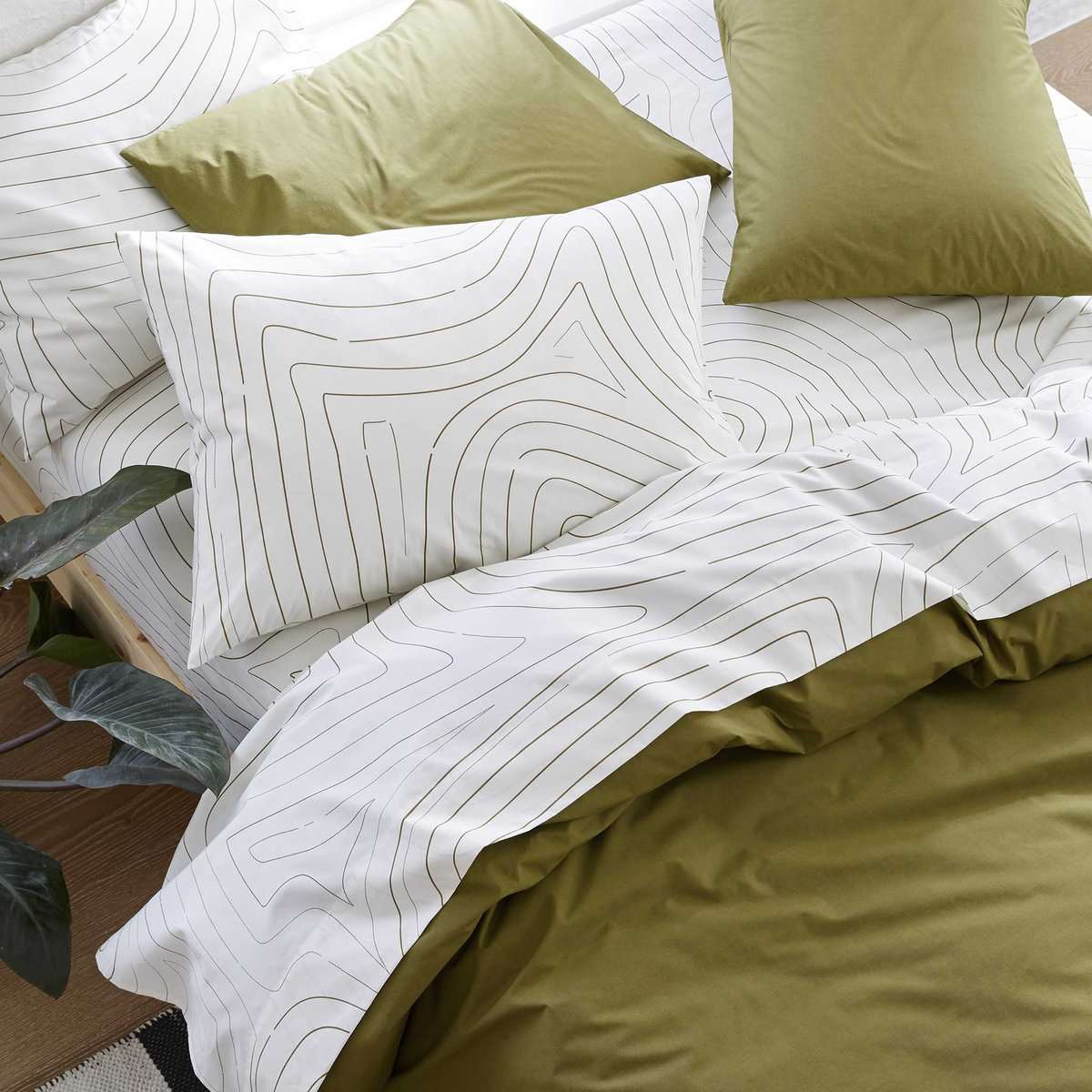 Bed with white sheets with wave motif and green duvet