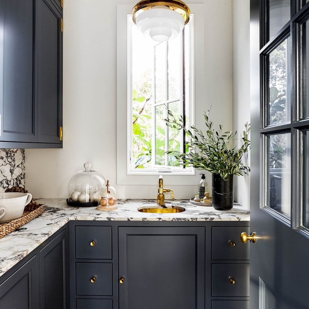A small narrow kitchen with indigo cabinets and gold hardware