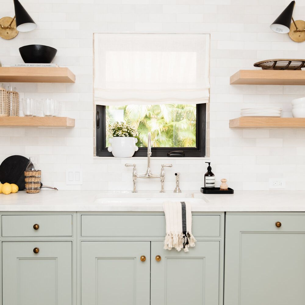 A kitchen with mint cabinets and wooden shelves