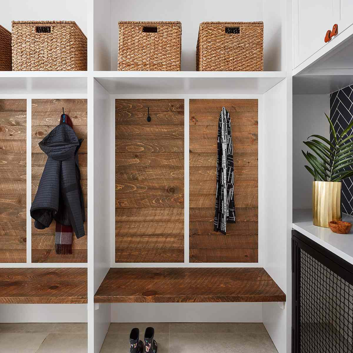 A mudroom with wood-paneled lockers and matching woven baskets
