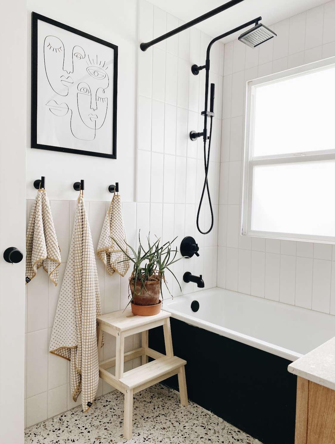 bathroom with terrazzo floor, black fixtures and a plant