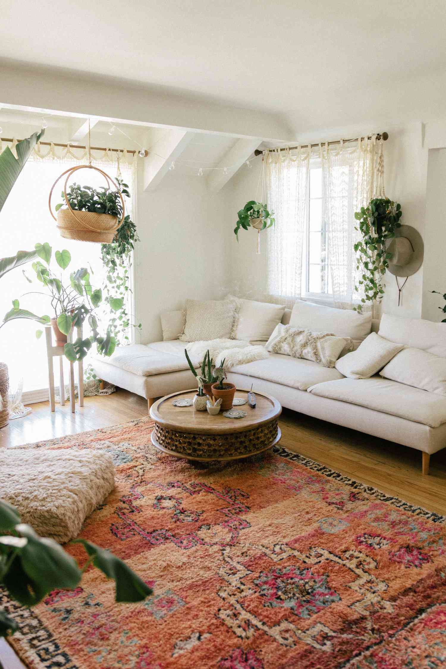 Living room with vintage patterned carpet, white couch, and hanging plants