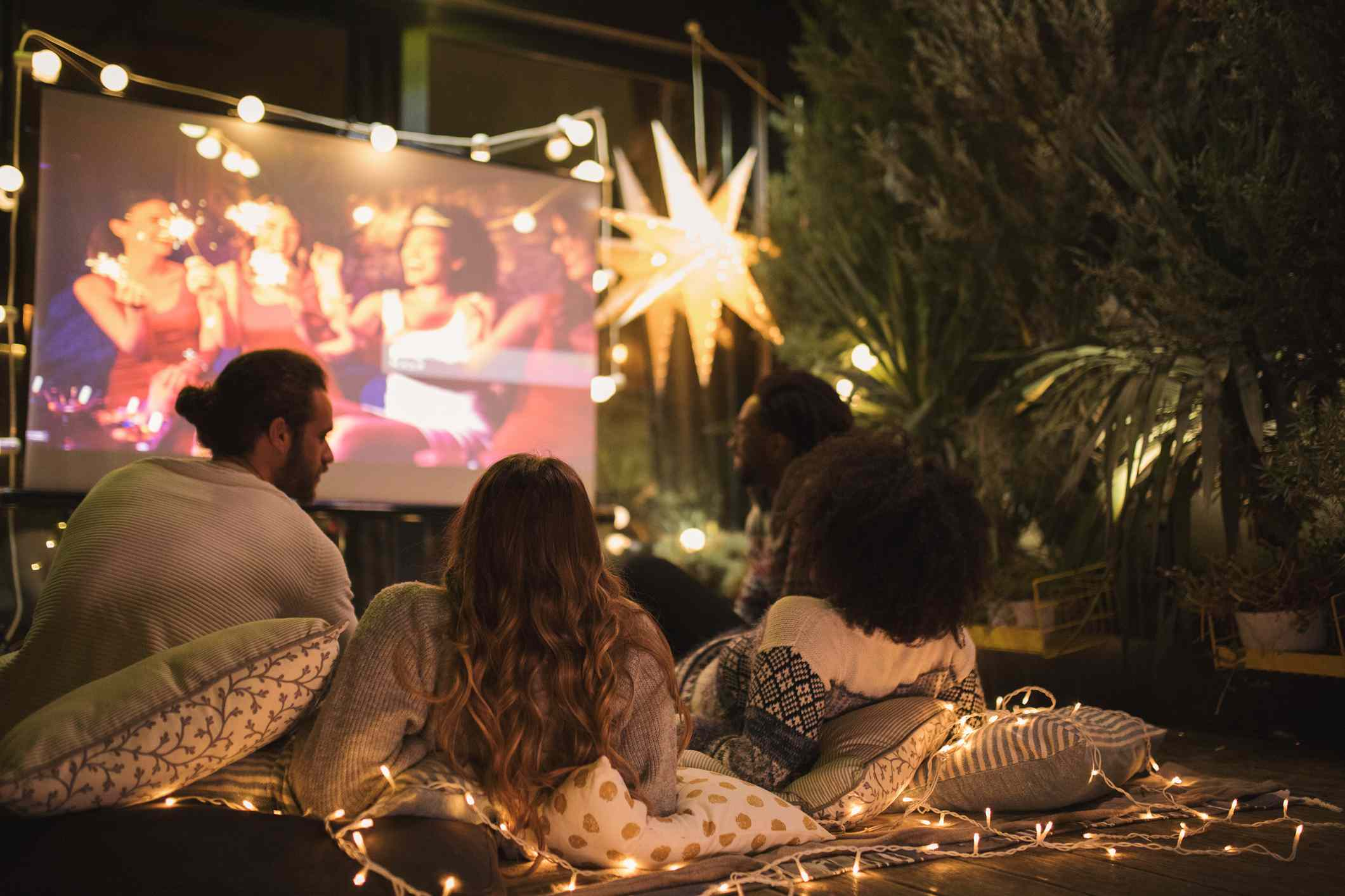Group of young people watch a projected movie outdoors
