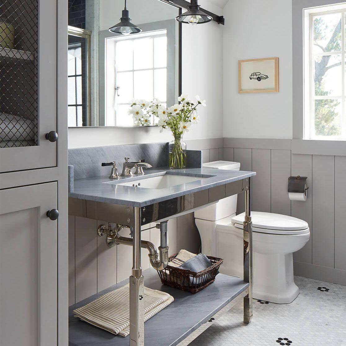 Tiled bathroom in gray and blue tones, industrial light fixtures