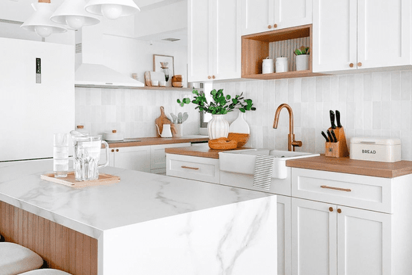 A small kitchen with white cabinetry, white countertops, and white pendant lights