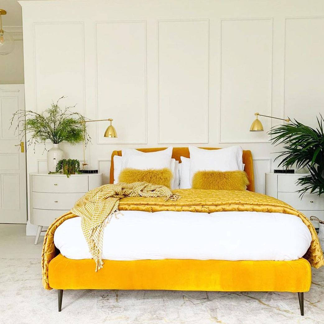 White bedroom with yellow bed and bedding