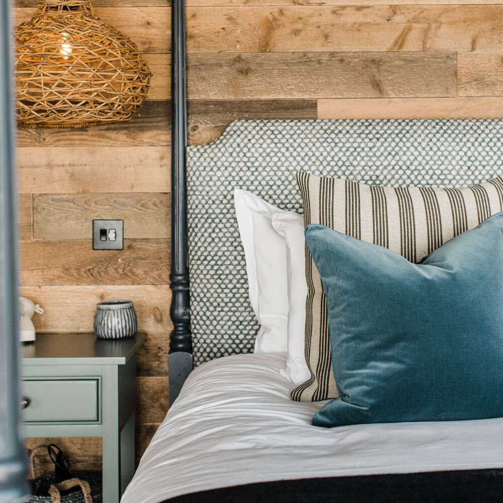 A canopy bed with a textured headboard and linens