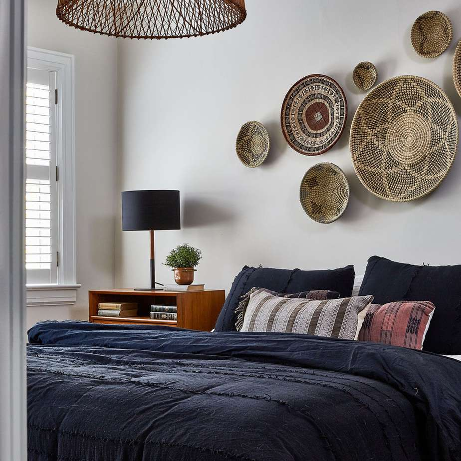 Light gray bedroom with wood and woven accents and navy bedding
