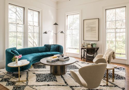 living room with rug and teal sofa