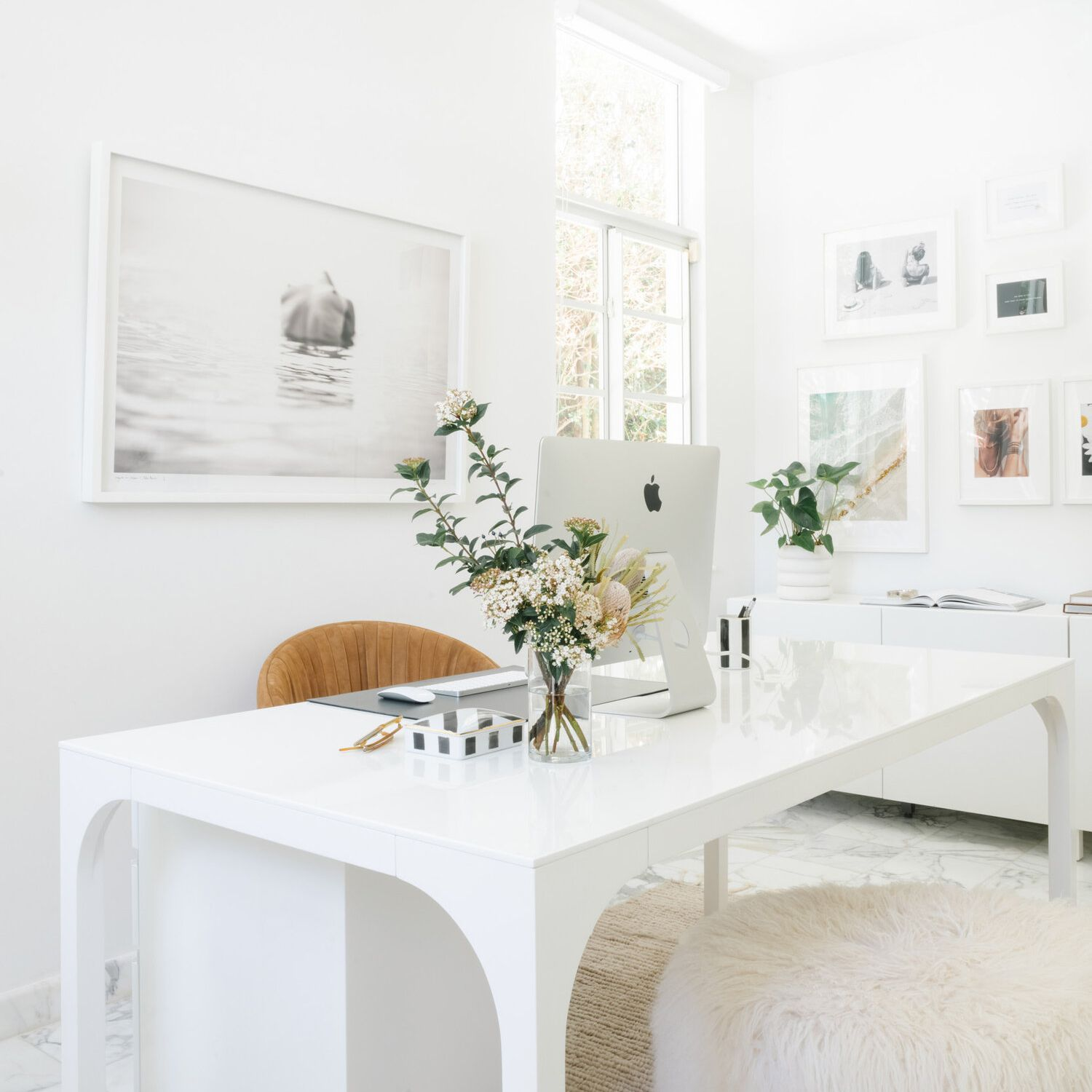 White beautifully styled desk with computer.