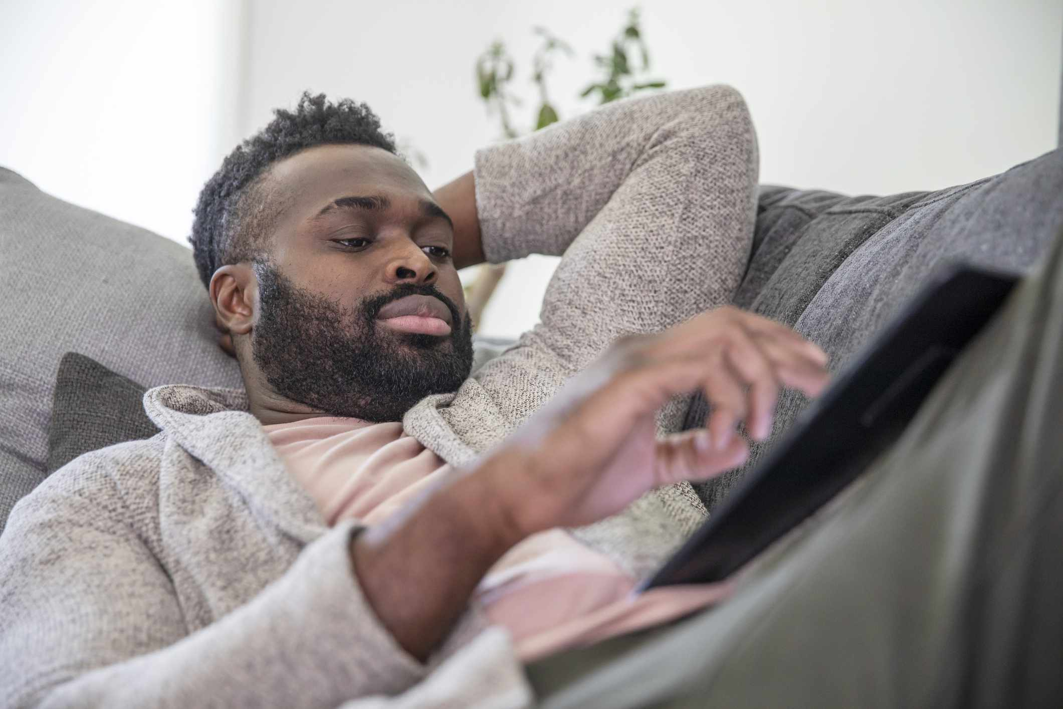 Man reclines on couch, watches tablet