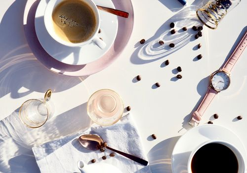 coffee with beans, glasses and a watch on white table