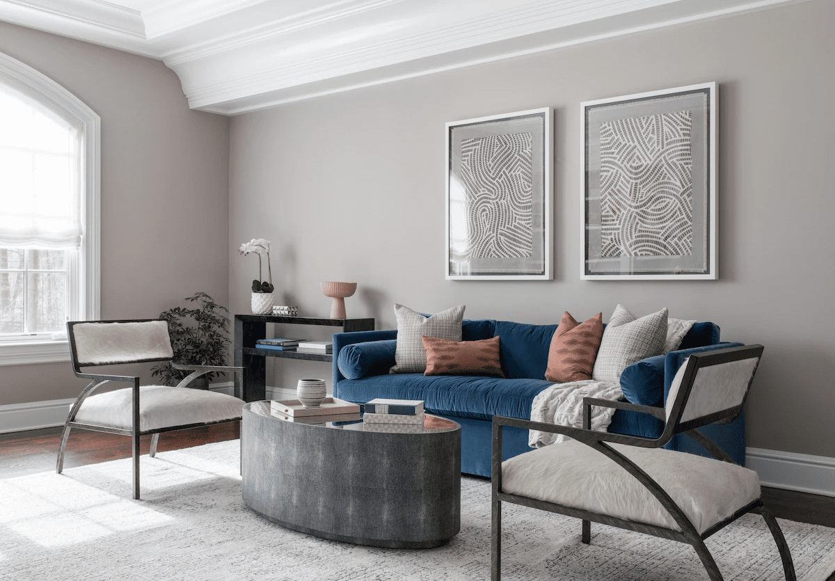 Well-curated living room with blue soft sofa, structural chairs and coffee table.