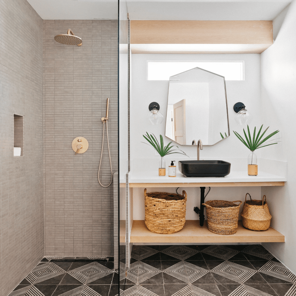 A bohemian bathroom lined with two kinds of gray tile
