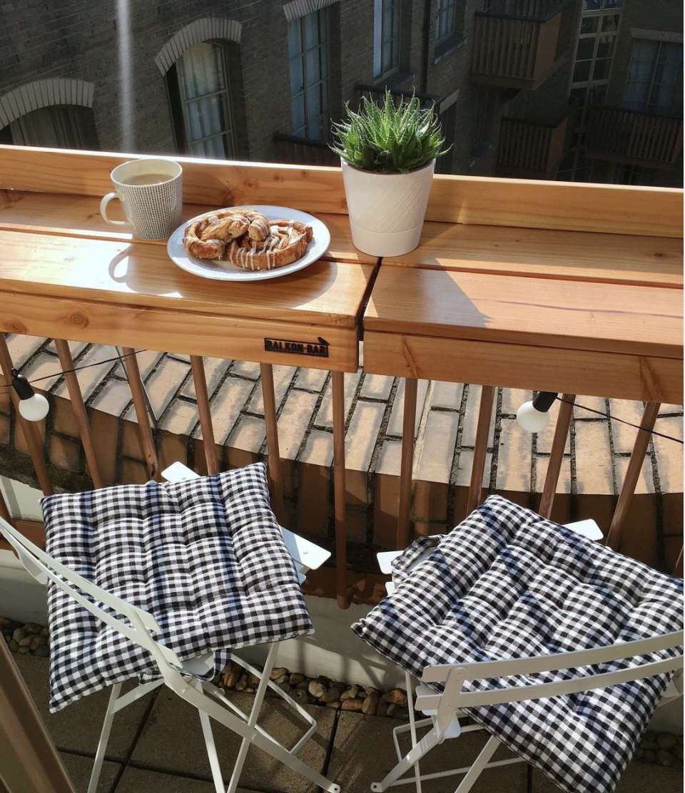wooden breakfast bar overlooking city, two chairs with plaid cushions, cup of coffee and plate of cinnamon rolls next to small plant