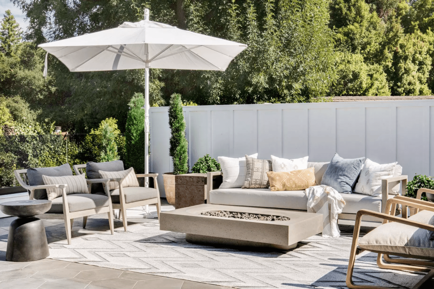 A deck decorated with plush chairs, an outdoor couch, and a large fire pit
