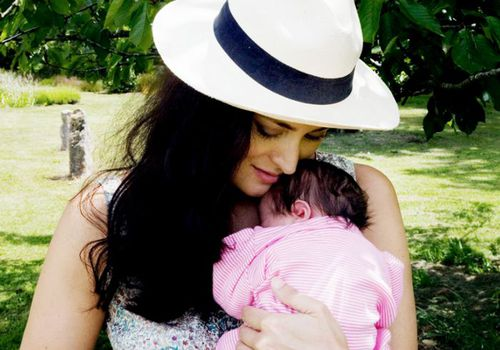 Woman in a hat holding a newborn baby