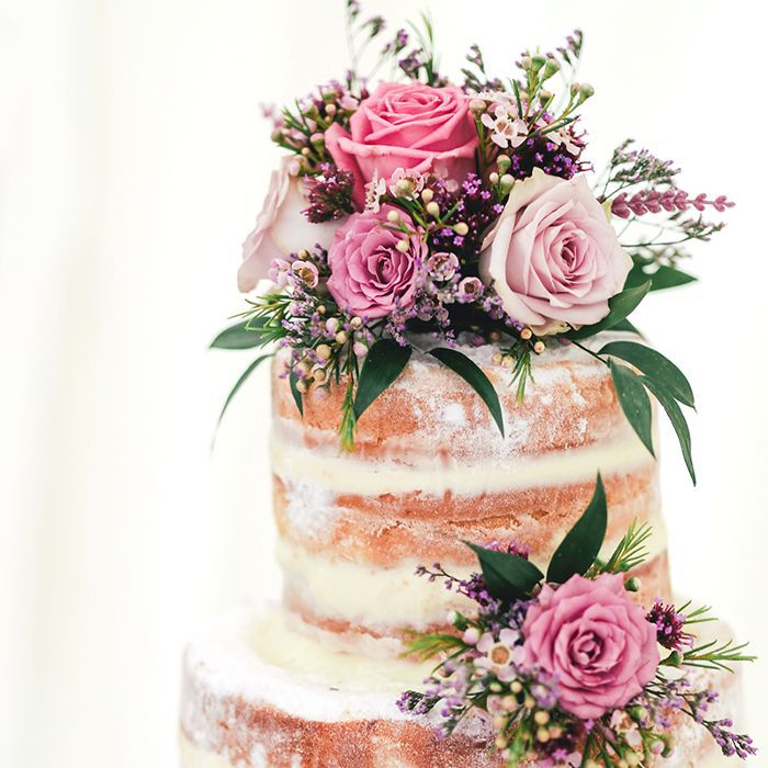 Multi-tiered wedding cake with pink flowers.