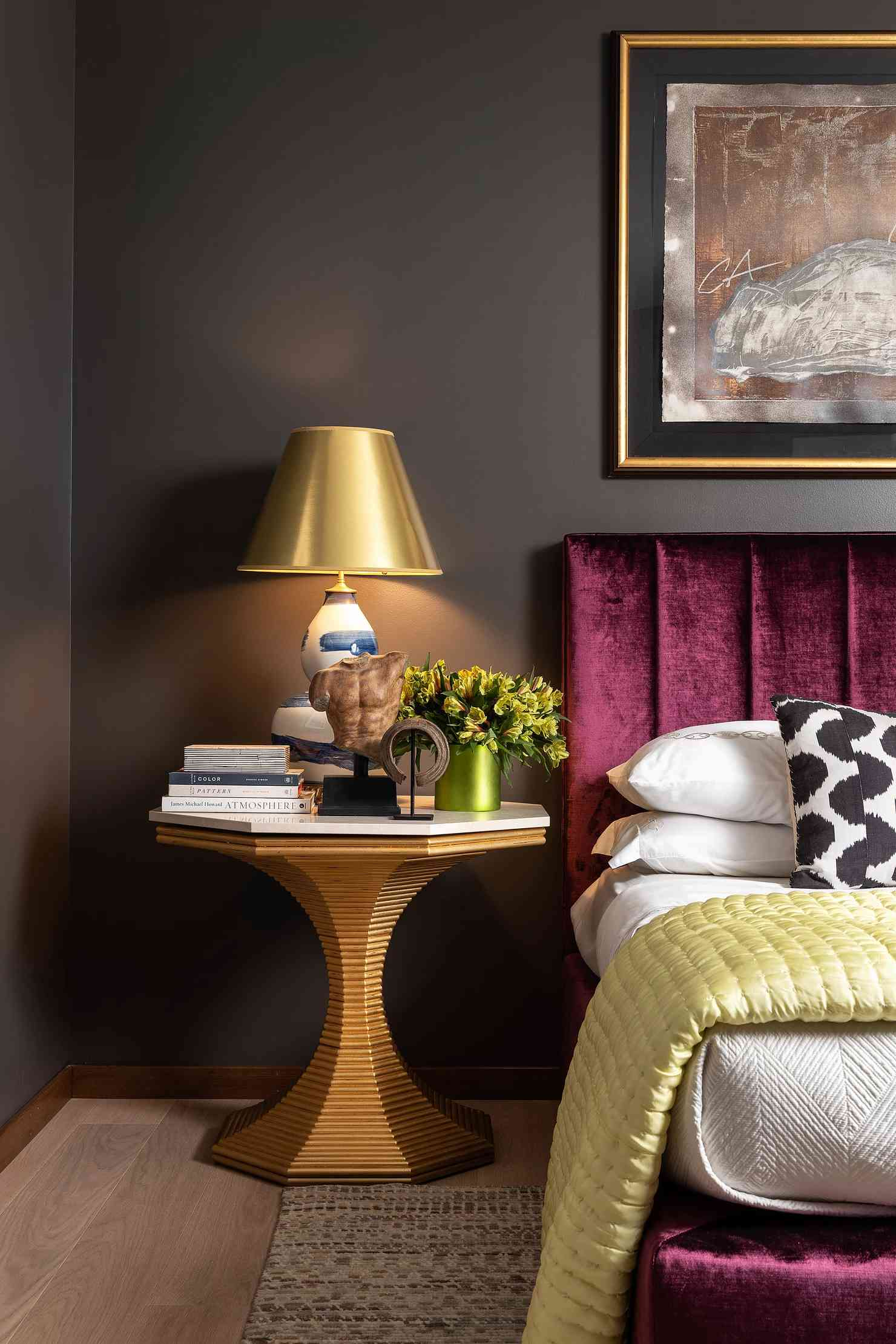 A dark bedroom with a luxurious velvet bed frame.