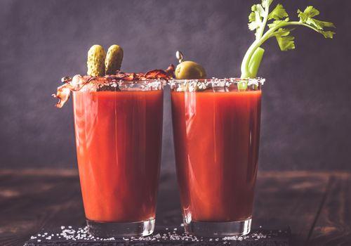 Dos vasos de Bloody Mary adornada con pepinillos y tallo de apio