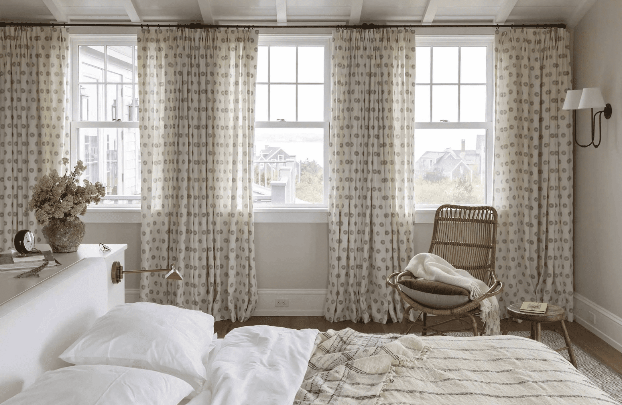 A bedroom with ivory printed curtains and ivory printed blankets