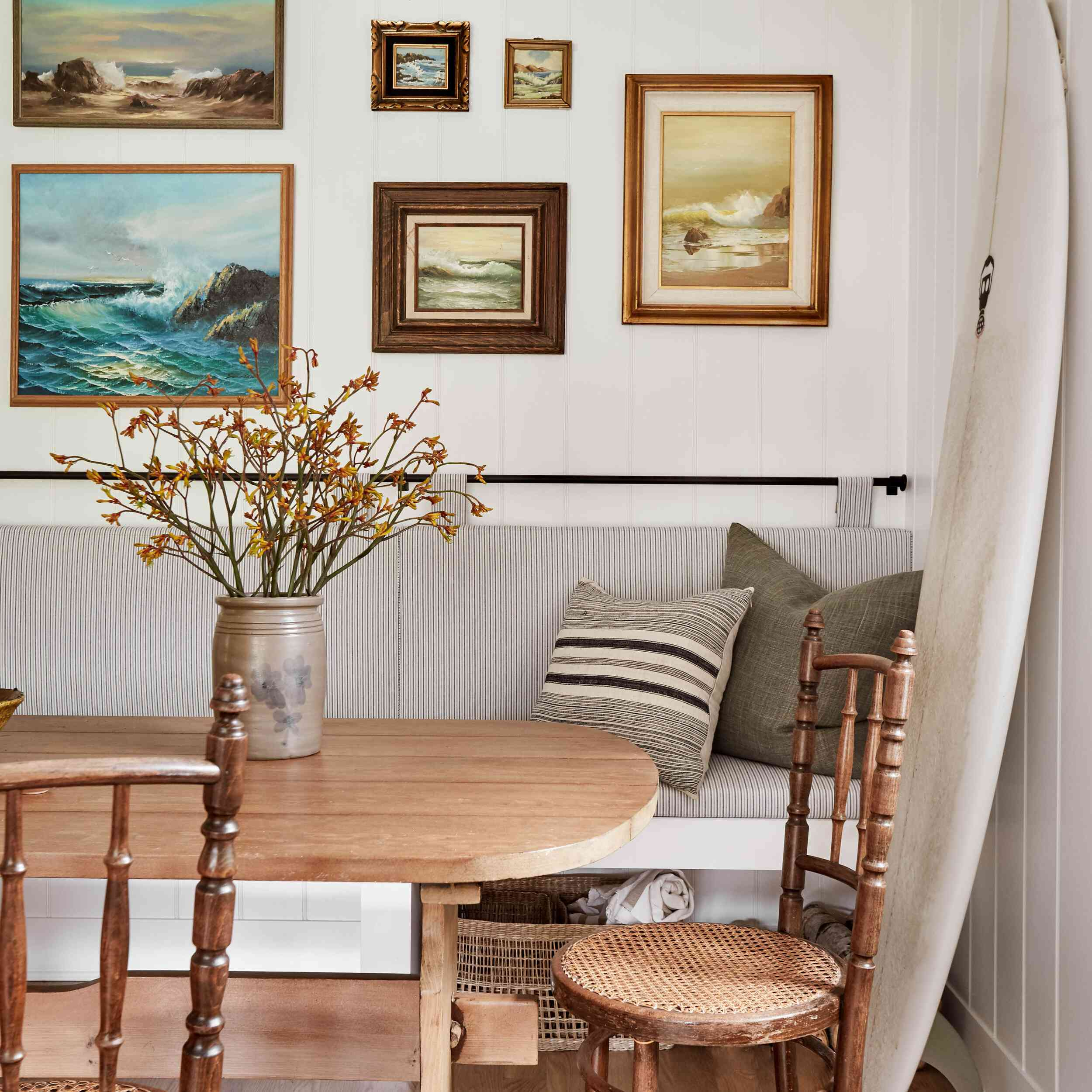 Surf-inspired cottage featuring art gallery wall in breakfast nook area