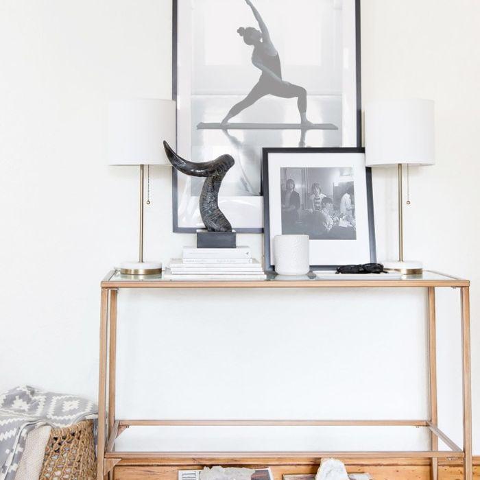 mesa auxiliar con arte, libros y lámparas