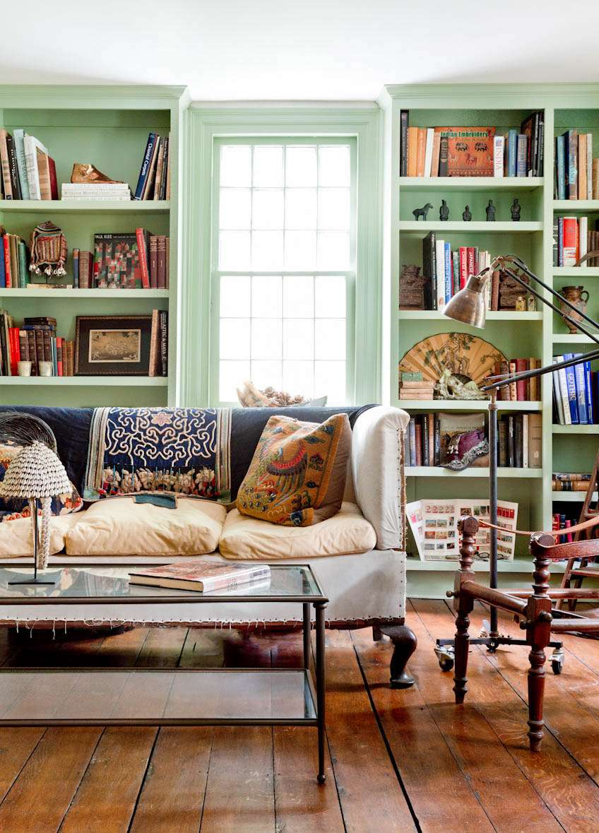 Eclectic living room with mint green bookshelves