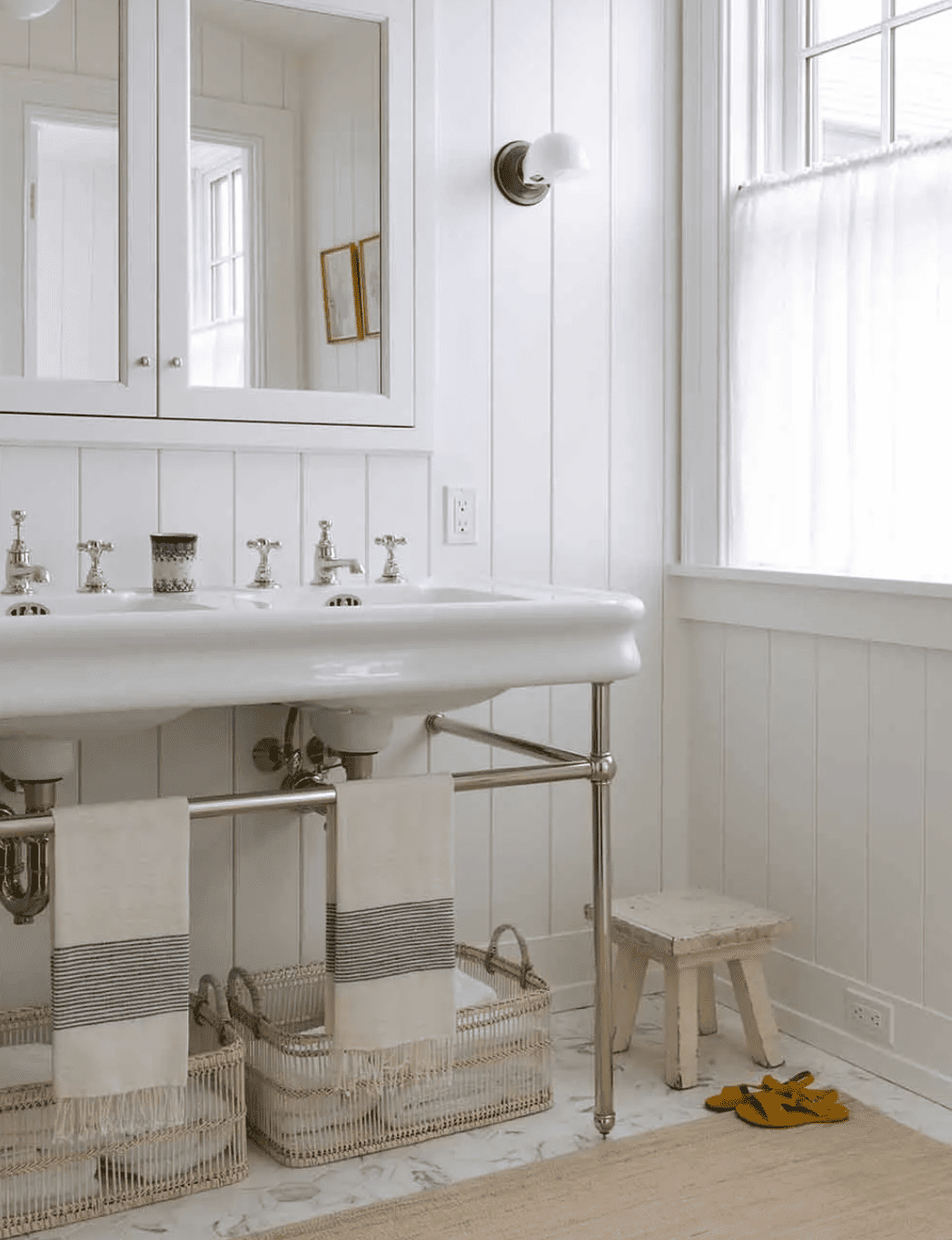 A small primary bathroom with a freestanding sink, a mirror-lined medicine cabinet, and two woven under-sink baskets