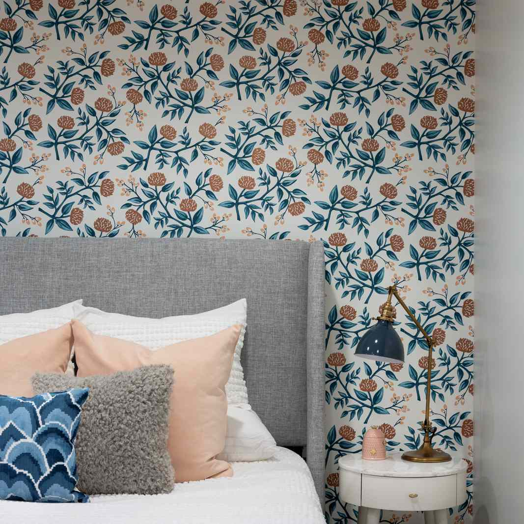 A bedroom with printed wallpaper and colorful pillows