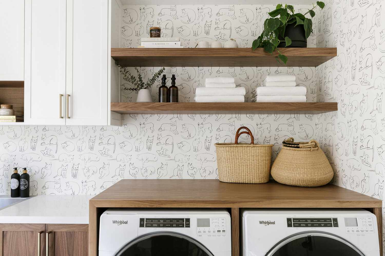 Laundry room with wall paper and shelving