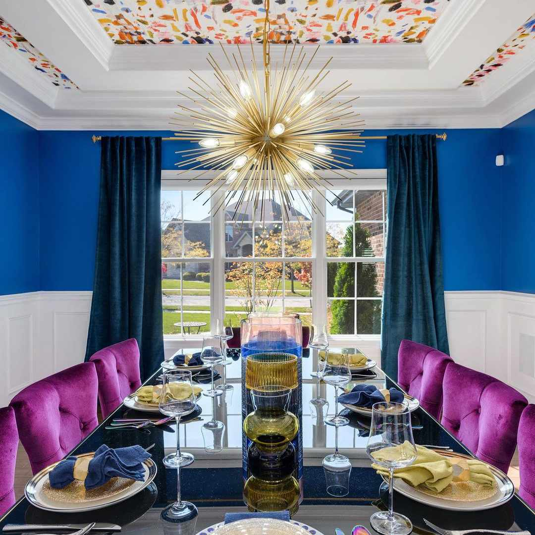 Glam dining room with bright purple chairs and a colorful wallpapered ceiling