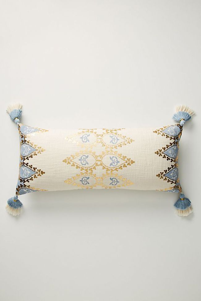 Neutral throw pillow with blue and gold embellishments.