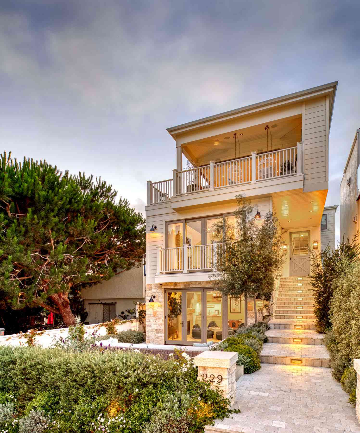 Tall exterior home with plants going up the stairs.