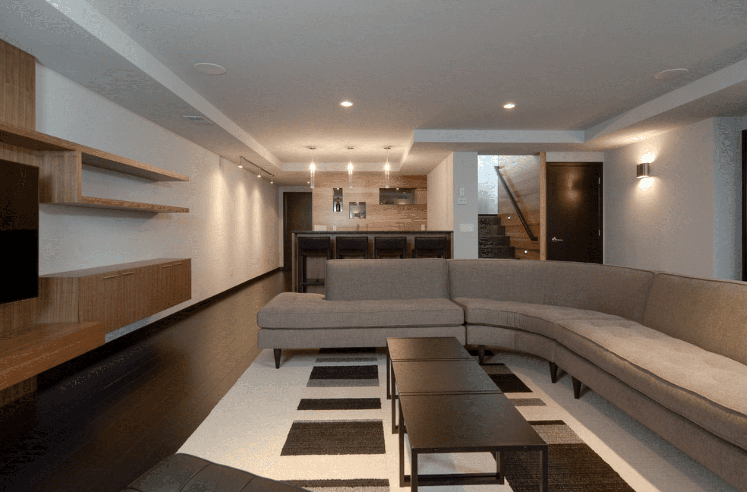 A basement lit with a combination of scones, pendant lights, and recessed lighting