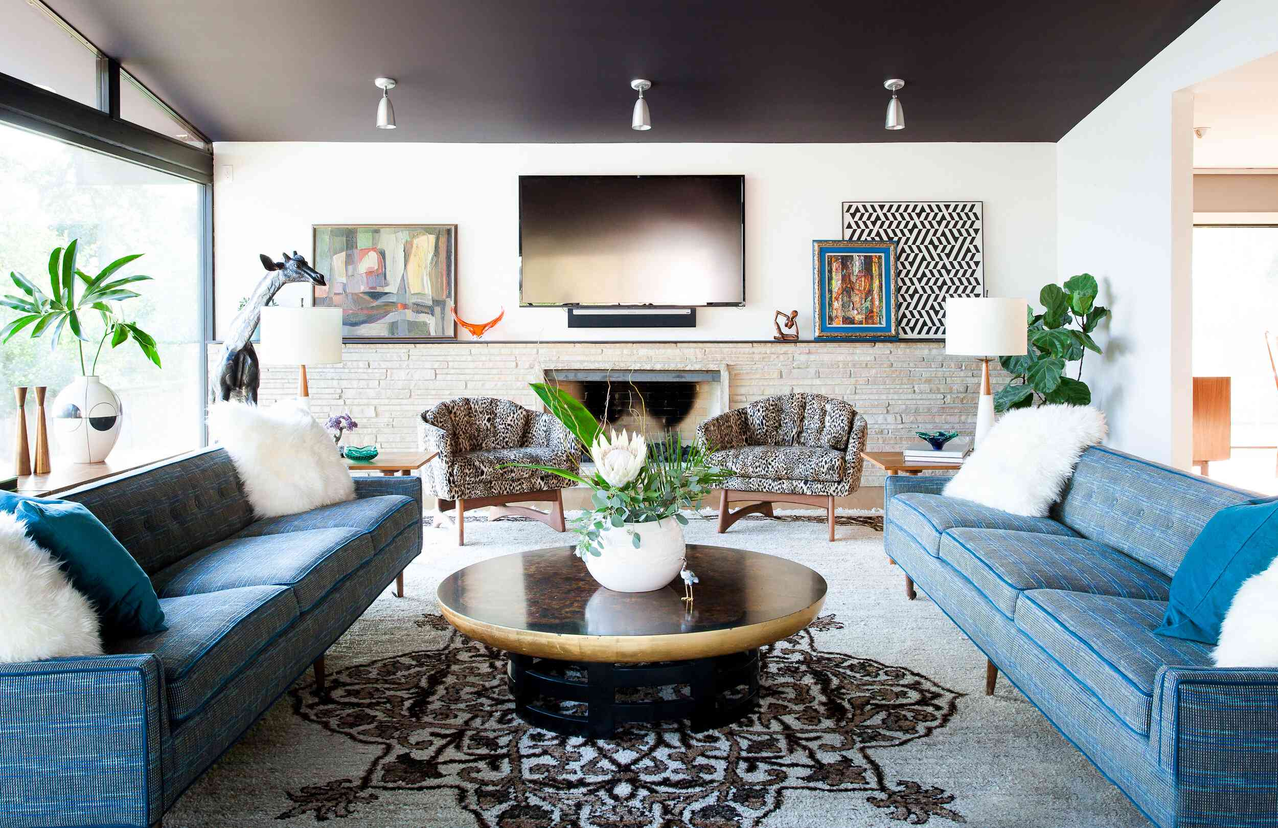 Eclectic living room with dark-painted ceiling, blue couches